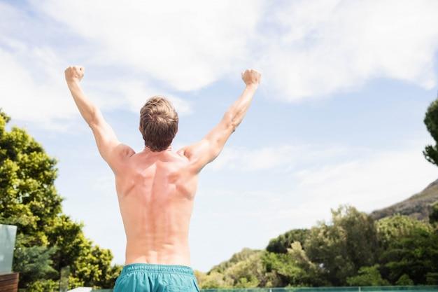 Vue arrière du jeune homme debout près de la piscine