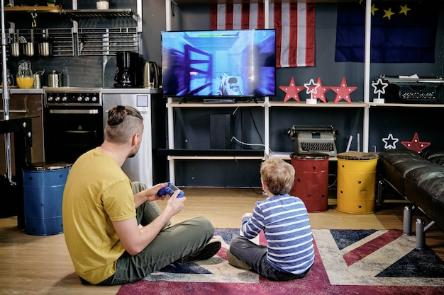 Vue arrière du jeune homme et du petit garçon jouant au jeu vidéo sur le sol