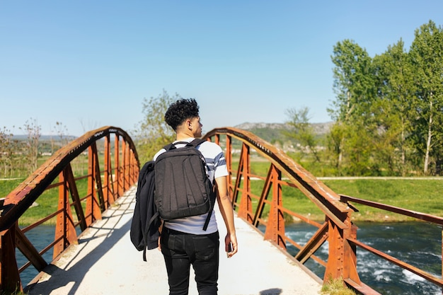 Vue arrière du jeune homme marchant sur le pont au-dessus de la belle rivière