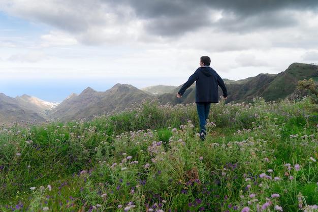 Vue arrière du jeune homme randonneur voyageur debout sur un chemin de montagne en terre dans la réserve naturelle sur un paysage de prairie verte par temps nuageux en veste chaude. concept de voyage, d'aventure, de randonnée et de motivation