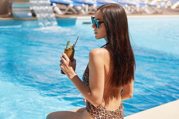 Vue arrière du jeune jolie femme buvant un cocktail contre la piscine extérieure. femme avec une peau bronzée parfaite assis près de la piscine