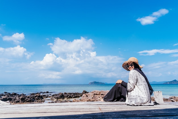 Vue arrière du jeune musulman à la recherche de passerelle en bois. futur et concept de recherche. femme debout sur la mer. concept de voyage.