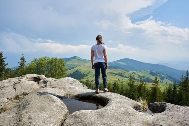 Vue arrière du jeune touriste femme debout sur un énorme rocher avec une grande flaque d'eau au milieu sous un beau ciel bleu bénéficiant d'une vue fantastique sur les montagnes