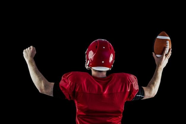 Vue arrière du joueur de football américain triomphant