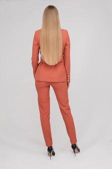 Vue arrière du modèle blonde en costume bleu clair.