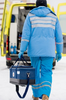 Vue arrière du paramédic en vêtements de travail bleus et gants médicaux transportant une trousse de premiers soins en allant vers la voiture d'ambulance