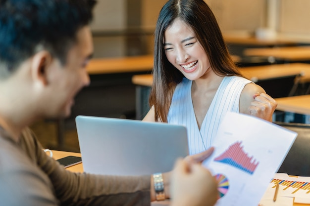 Vue arrière du patron félicitant une femme d'affaires asiatique dans une action heureuse en cas de succès