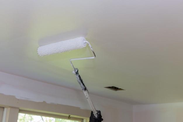 La vue arrière du peintre peint le plafond avec un rouleau dans la chambre