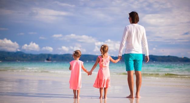 Vue arrière du père et de deux filles marchant sur une plage blanche tropicale