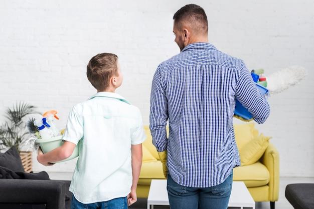 Vue arrière du père et du fils posant avec des produits de nettoyage