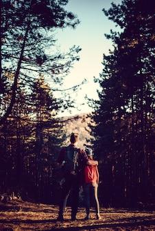 Vue arrière du père et de la fille debout enlacés dans la forêt