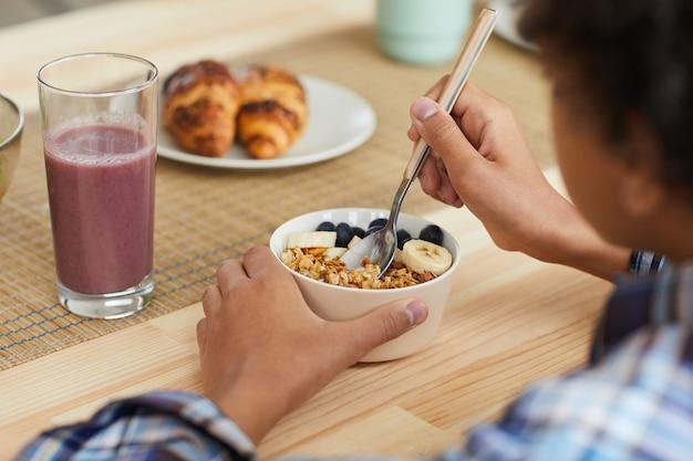 Vue arrière du petit garçon assis à la table et manger des céréales avec des baies et boire du jus de fruits frais, il prend son petit déjeuner