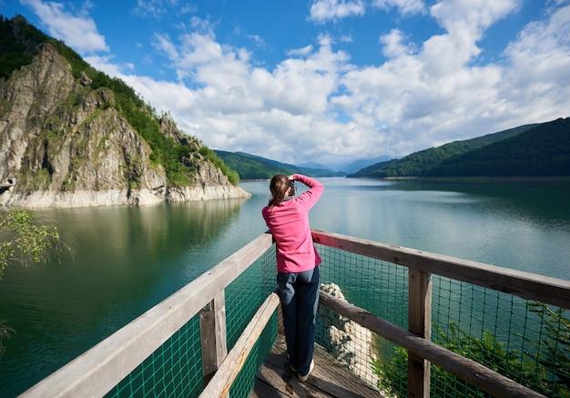 Vue arrière du photographe femelle sur le lac vidraru carpathians romania