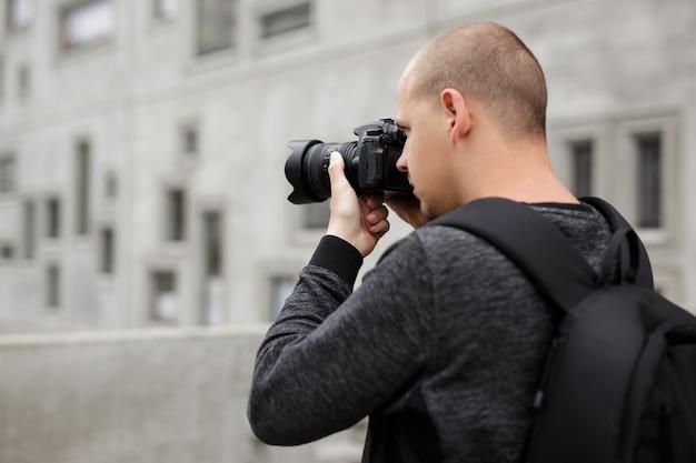 Vue arrière du photographe masculin prenant une photo avec un appareil photo reflex numérique professionnel moderne sur fond de bâtiment en béton