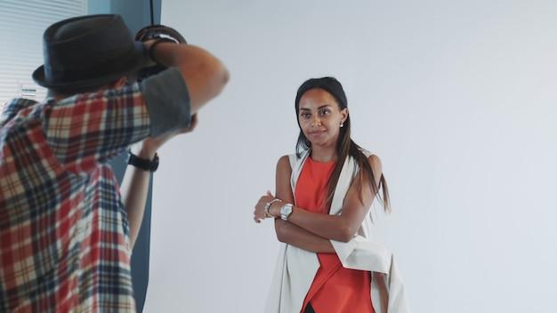Vue arrière du photographe prenant une photo de beau modèle multiracial en studio