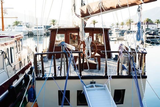Vue arrière du pont des capitaines sur un yacht à voile blanc amarré à côté d'autres bateaux