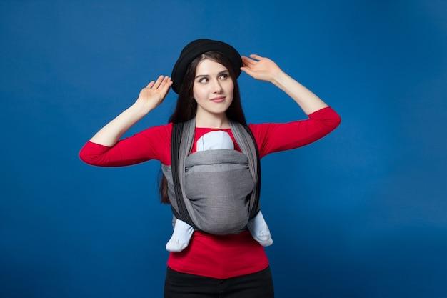 Vue arrière du portage attrayante jeune mère avec bébé dans un porte-bébé tissé fixant son chapeau. idée de concept mains libres et maternité active