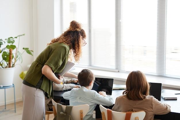 Vue arrière du portrait de deux écoliers utilisant des ordinateurs portables en classe informatique, espace de copie