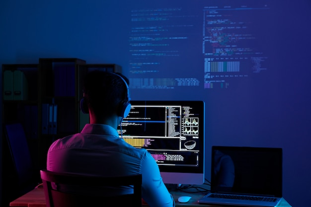 Vue arrière du programmeur travaillant toute la nuit