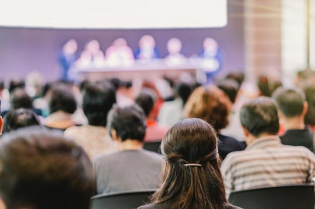 Vue arrière du public dans la salle de conférence ou la réunion de séminaire avec des conférenciers