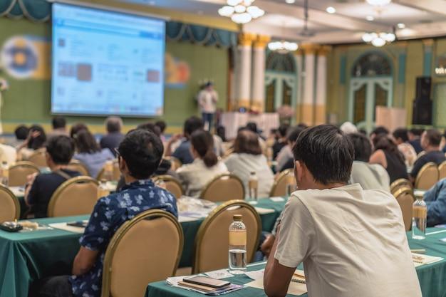 Vue arrière du public écoutant les conférenciers présenter la diapositive sur la scène dans le confère
