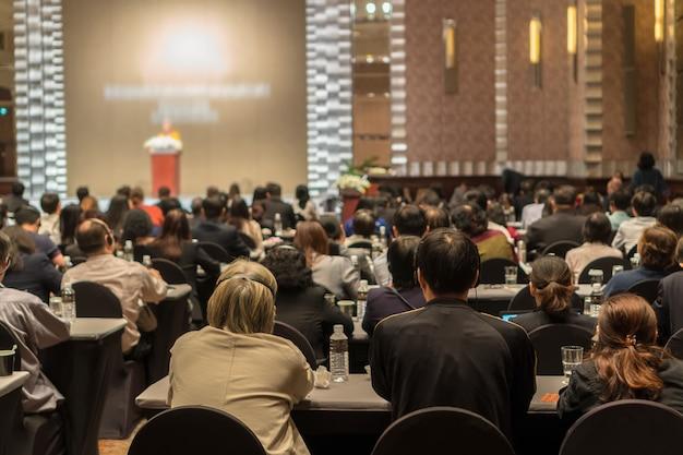 Vue arrière du public portant et écoutant des haut-parleurs via un casque d'interprétation sur la scène