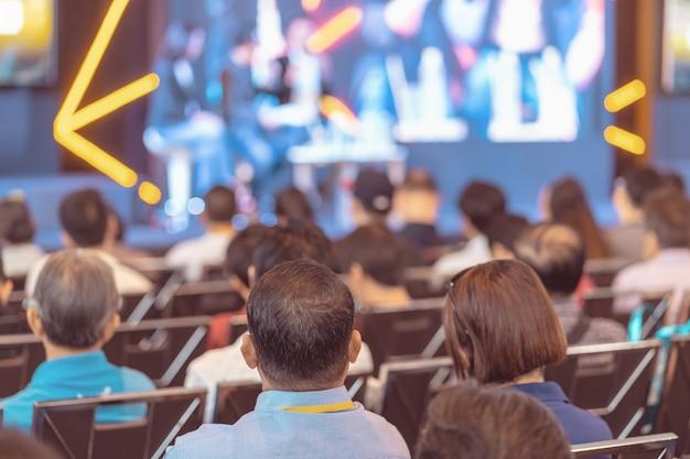 Vue arrière du public qui écoute les orateurs sur la scène dans la salle de conférence