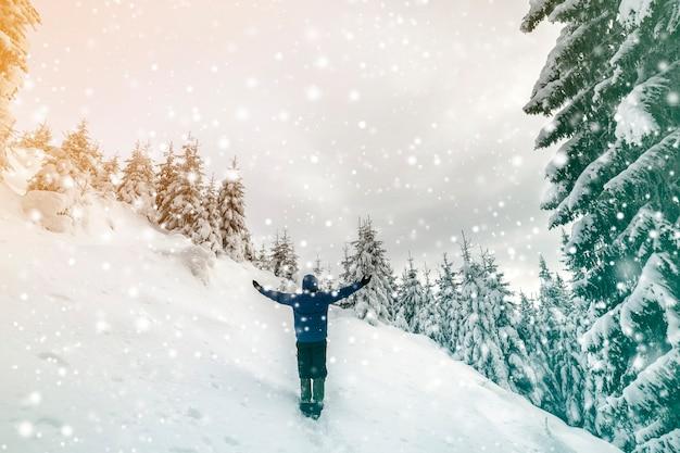 Vue arrière du randonneur touristique debout avec les bras levés sur une pente de montagne escarpée