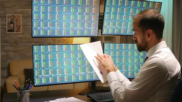 Vue arrière du trader boursier au bureau à domicile. zoom avant.