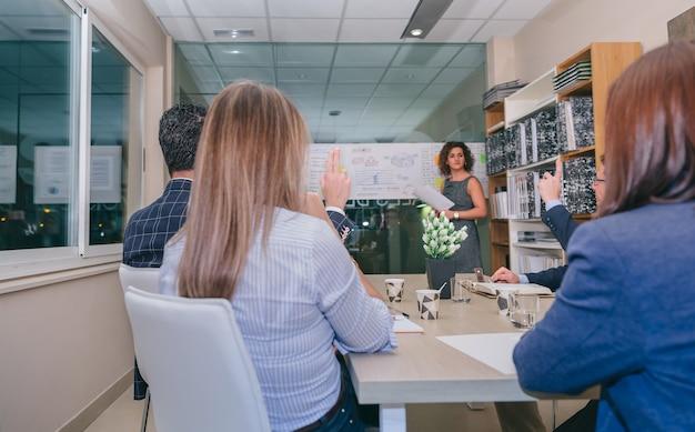 Vue arrière du travail d'équipe avec les doigts levés pour poser des questions à l'entraîneur féminin après une réunion d'affaires au siège