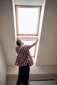 Vue arrière du travailleur s'appuyant sur un ruban à mesurer sur la fenêtre