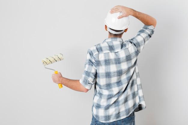 Vue arrière du travailleur tenant un rouleau à peinture