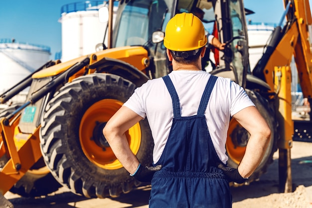 Vue arrière du travailleur en uniforme regardant l'excavatrice en se tenant debout dans la raffinerie.