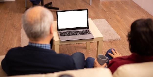 Vue arrière du vieux couple dans leur salon à la recherche d'un ordinateur portable avec une maquette isolée blanche.