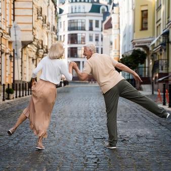 Vue arrière du vieux couple heureux dans la ville