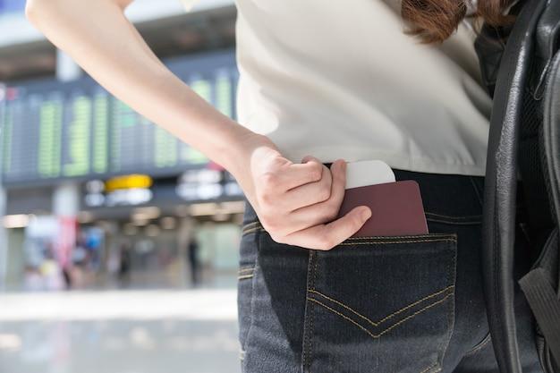 Vue arrière du voyageur asiatique avec passeport à l'aéroport