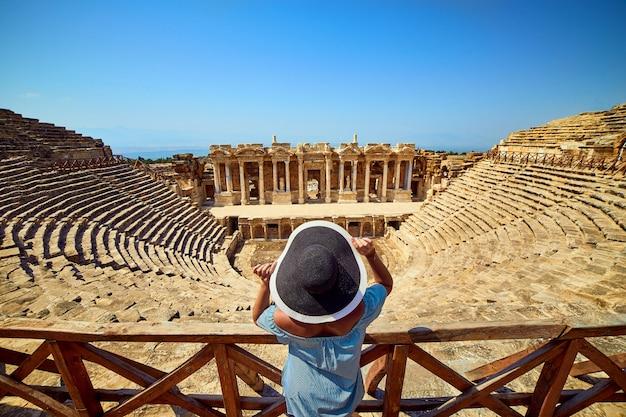 Vue arrière du voyageur femme au chapeau à la recherche de superbes ruines de l'amphithéâtre dans l'ancienne hiérapolis, pamukkale, turquie. grand panorama