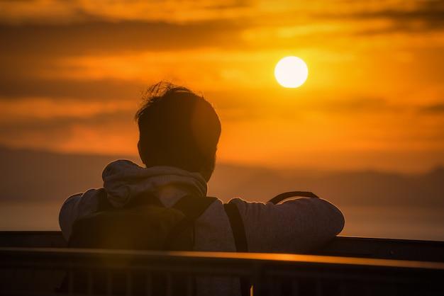 Vue arrière du voyageur homme regardant la mer au coucher du soleil à shizuoka, japon.