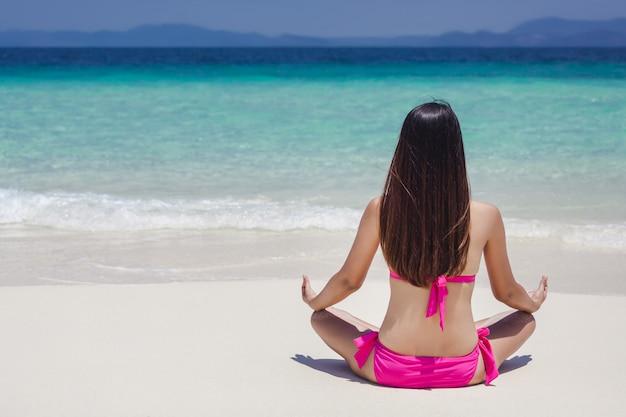 Vue arrière du yoga femme sur la plage