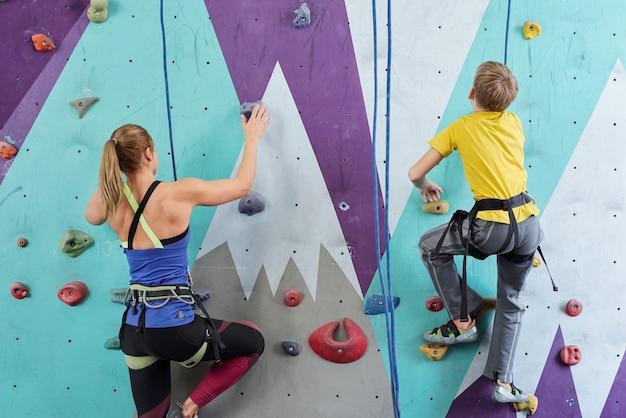 Vue arrière de l'écolier et jeune femme en vêtements de sport saisissant par de petites roches sur un mur d'escalade pendant l'entraînement sportif