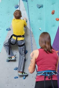 Vue arrière de l'écolier en vêtements de sport se déplaçant vers le haut sur le mur d'escalade tandis que l'instructrice debout à proximité et tenant la corde