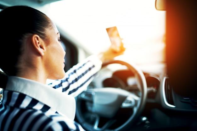 Vue arrière d'une élégante jeune fille faisant un selfie dans la voiture.