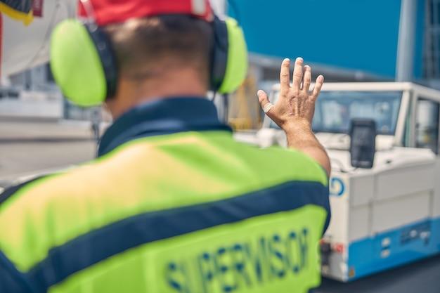Vue arrière d'un employé de l'aéroport dans des écouteurs dirigeant un conducteur de refoulement à l'aérodrome