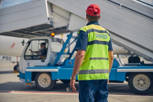 Vue arrière d'un employé de l'aéroport supervisant son collègue conduisant un camion avec les escaliers d'embarquement des passagers