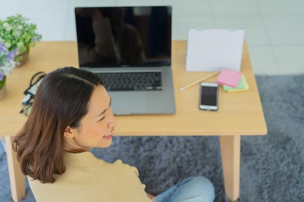 Vue arrière employé femme assise devant un ordinateur portable sur la table pour travailler dans la maison pour le travail à domicile