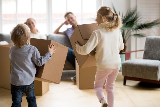 Vue arrière des enfants jouant avec des boîtes le jour du déménagement
