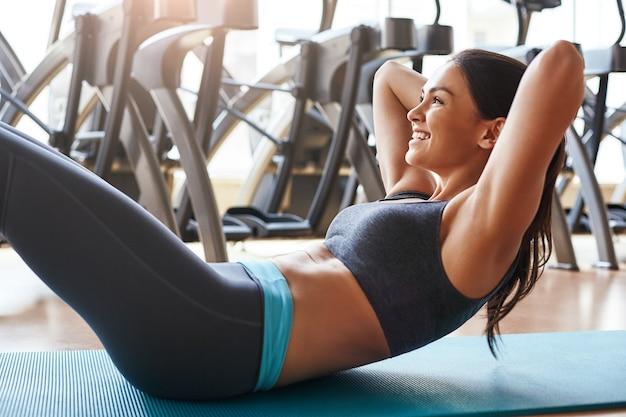 Vue arrière de l'entraînement de finition d'une jeune femme courte et mince en tenue de sport debout au gymnase