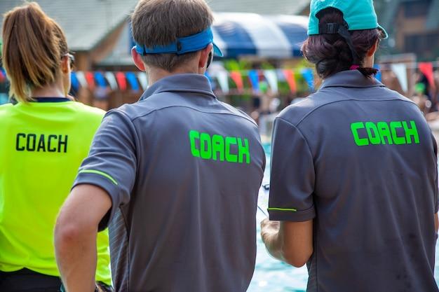Vue arrière des entraîneurs de natation masculins et féminins, portant une chemise coach, à une piscine extérieure