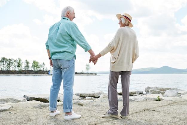 Vue arrière des époux seniors occasionnels contemporains tenant par les mains en se tenant debout au bord du lac le jour d'été