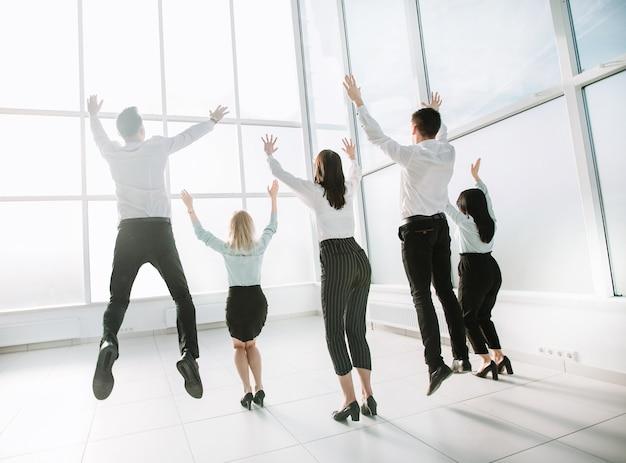 Vue arrière. équipe commerciale heureuse, s'amusant dans un nouveau bureau lumineux. le concept d'une startup